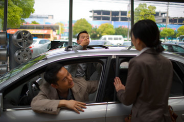 Young boy blowing his mother a kiss through the sunroof of a car inside a car showroom.