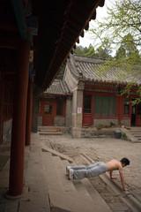 Young adult man doing press-ups outdoors.