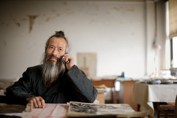 Mature adult man wearing traditional oriental clothing while talking on a cellphone.