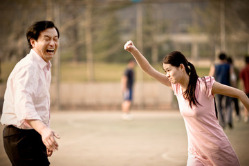 Mid-adult man having fun with his young adult daughter on a basketball court.