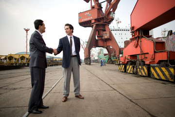 Young adult businessman shaking hands with a mid-adult male colleague at shipping yard.