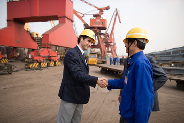 Young adult businessman shaking hands with a mid-adult foreman at a shipping yard.