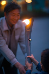 Young boy handing an Olympic torch to his mature grandfather in a park.
