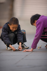 Young boy playing with folded paper in the street.