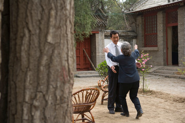 Mid-adult businessman greeting his senior mother outside.