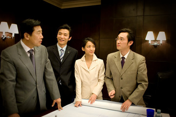 Young adult business woman standing with three male colleagues looking at plans in a boardroom.