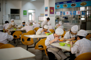 Young male chefs sitting eating in a canteen.