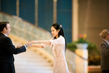 Young adult couple dancing in a hotel lobby.
