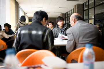 Teenage boy sitting in a cafeteria with friends and a senior male teacher.