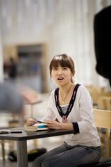 Teenage girl sitting in a study hall.