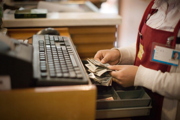 Money being placed into a till of a register.