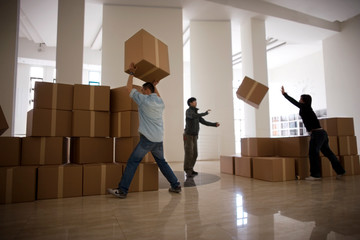 Three young adult men stacking boxes to carry.