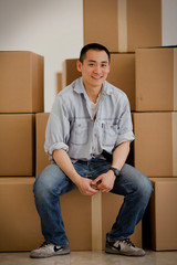 Portrait of a young adult man with boxes in a building.
