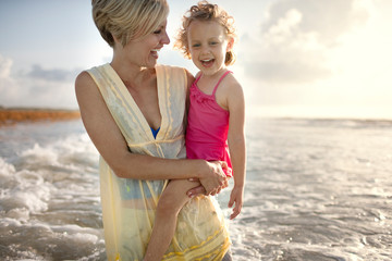 Mother holding her daughter in the waves at the beach.