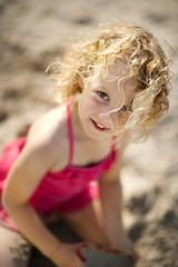 Portrait of a young girl playing in the sand at the beach.
