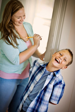 Mid-adult woman measuring her son up against a wall.