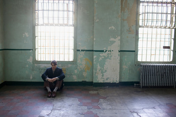 Young adult business man sitting on the floor of a derelict building with his arms around his knees.