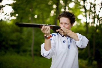 Woman aiming rifle in forest