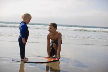 Boy teaching his young brother skim boarding at a beach.