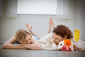 Happy lesbian couple lying on bare floorboards and looking at each other inside their home.