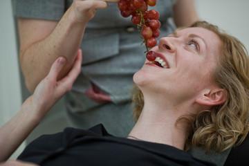 Women lying on floor of house eating grapes