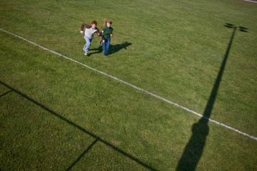 Young teenage couple running side by side across a sports playing field.