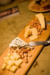 Wooden platter laid with nuts and cheese.