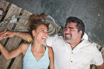 Laughing mid-adult couple sharing a joke while lying on their back on a wooden jetty.