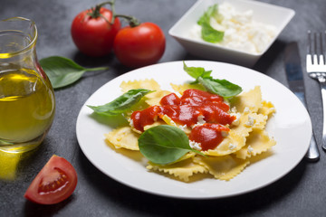 Boiled ravioli with basil, cheese and tomato sauce on a black background