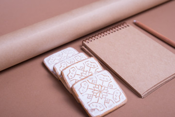 A blank notebook with Christmas cookies and wrapping paper on table, close up