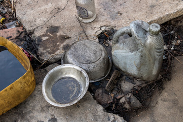 Oily Metal Bowls with Old Grey Plastic Diesel Oil Bottle on Dirty Floor - Recycling