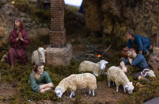 Nativity set with shepherds resting and sheep eating grass. Christian religion, Christmas holiday season decoration scene concepts