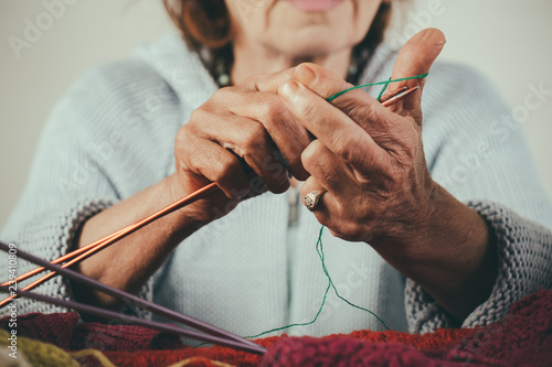 Women's hands making christmas socks. Gifts for Knitters. Winter colours. Close-up of grandmother hands. Vintage knitting needles in hands of a woman