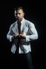 Sexy man is buttoning a white shirt. Young bearded sexy man. White man in white shirt on black background. Young attractive businessman thinking before work. Dream of success