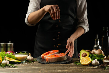 The chef prepares fresh salmon fish, smorgu trout, sprinkling black pepper with the ingredients. Frost in the air. cooking fish food. Salmon steak. Cooking vegan cuisine, restaurants, hotel business