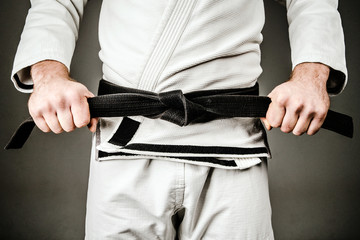 Midsection of Man in A Gi holding Black Belt tied Around His Waist.