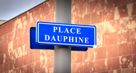 blue street sign where it is written in French Dauphine Square