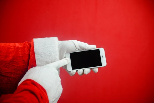 Santa showing mobile phone during holiday time, mockup electronic communications technology equipment background. Closeup image of hands working with video or photography on smart telephone.