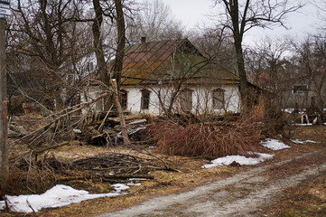 Old unkempt house in the countryside. Living standard. Cloudy winter day. Authentic architecture. Ukraine Kiev region.