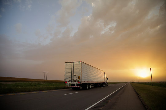 A semi truck drives towards the sunset on a interstate highway