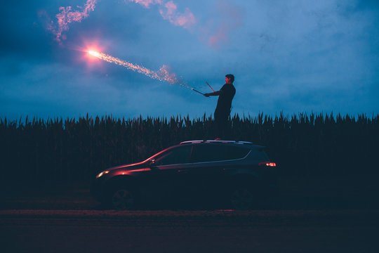 A man shoots fireworks off of the roof of his SUV car in a corn field