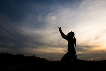 Silhouette of woman praying with god