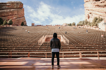 Symmetrical Portrait of Male Person Standing Front and Center on Stage Dreaming and Imagining while Facing Stadium Stands Seating at Outdoor Amphitheater Concert Music Hall on Clear Blue Sunny Day