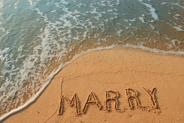 The word marry handwriting on sand beach with blue waves background.