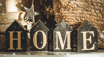 Home decorations in the wooden background of a letter with an inscription home. Christmas decorations and snow. Winter reading.