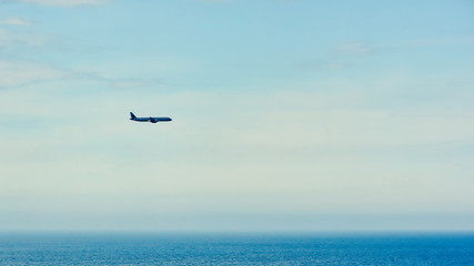Silhouette of a plane flying against a clean blue sky over the ocean . copy space for text