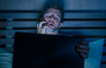 man alone in bed playing cybersex using laptop computer watching porn sex movie late at night with lascivious pervert face expression in internet pornographic sexual content