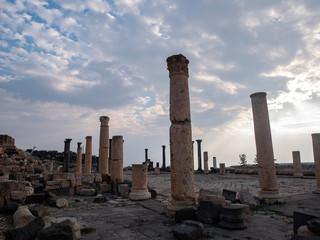 Pillars of a Roman temple against a dramatic sky