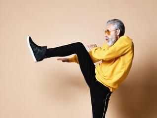 Old brutal senior millionaire man make a punch hit with leg in aviator sunglasses stylish fashionable men