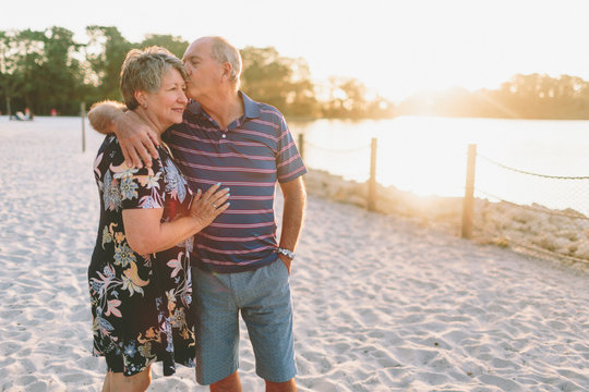 A senior couple together on the beach at sunset.